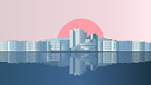 The city is reflected in the water, the sun rises outside the city against the dawn sky in a horizontal format