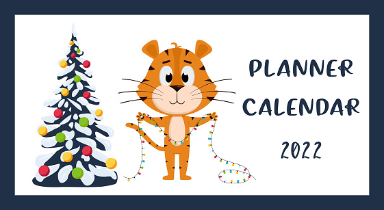 The cover of the Horizontal desktop calendar for 2022. The symbol of the year in the Chinese calendar. The Year of the Tiger. Tiger stands with a garland near the Christmas tree.