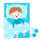 The cute brown-haired little boy in blue pajama lovely sleeping under the duvet in bed top view. Blue slippers lie near the bed. Isolated vector illustration on white background in cartoon style