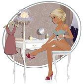 Pretty girl sitting at her dressing table putting moisturiser on her legs.