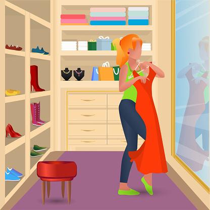 The girl tries on a dress near the mirror. Wardrobe.