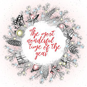 The most wonderful time of the year Christmas card with sketch elements. Berry, ball, star, box, pinecone, fir branches.