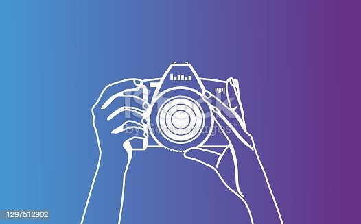 istock The photographer is holding a camera and is preparing to take a photo. White vector hands contour on a violet blue background. Logo for operators, reporters 1297512902