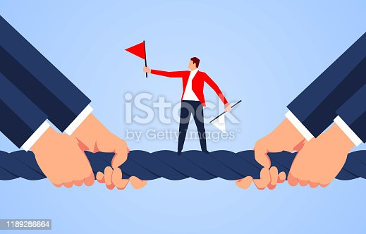 istock The referee stands in the middle of the rope of the tug-of-war 1189286664