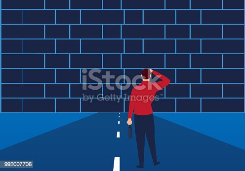 The road ahead of the businessman is blocked by the wall