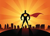 A silhouette style illustration of a superhero standing with a city skyline in the background. Objects are layered and grouped for ease of editing. Wide copy space available for your logo or text.