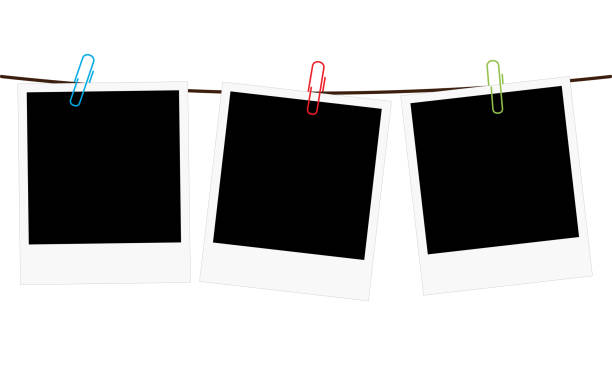Three blank polaroid frames hanging on a rope Vector illustration of three empty blank photo polaroid frame slides hanging on a rope with colorful paperclips over white background polaroid frame stock illustrations