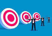 Three businessmen holding bows and standing in a row ready to shoot bullseye