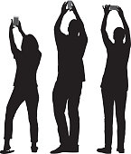 Vector silhouettes of three people taking pictures with their smart phones.