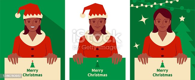 istock Three smiling beautiful teenage girls dressed in a Santa Claus suit holding a blank sign 1286280932