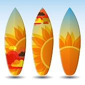 Three surfboards with sunshine designs on