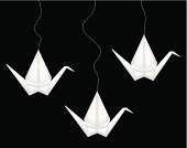 Three white origami cranes hanged by a rope on a black background. Some are decorated with flower patterns.