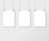 Three white poster on brick wall