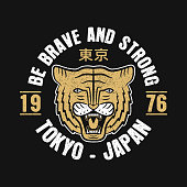 Tokyo, Japan typography graphics for slogan t-shirt with japanese tiger. Tee shirt print with grunge and inscription in Japanese with the translation: Tokyo. Vector illustration.