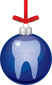 Vector illustration of a shiny dark blue glass christmas ornament with a tooth on it hanging from a red ribbon.