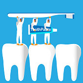 Three medical professionals work together to carry toothbrush and toothpaste over teeth, symbolizing tools used to care for teeth.