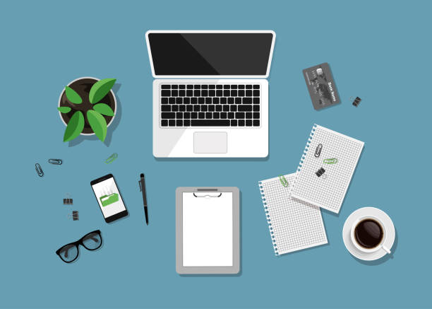 Top view of business workplace on blue background. Flat design of workspace with laptop, notebook, cup of coffee, pot of plant, eyeglasses etc isolated on blue surface. Vector illustration. overhead stock illustrations