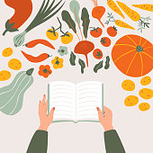 Top view of cartoon cookbook in hands on the table surrounded by various vegetables. Vegan food Recipe vector concept isolated from light background