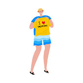 Tourist man in blue shorts is photographed with a yellow t-shirt in his hands. Vector illustration in flat cartoon style