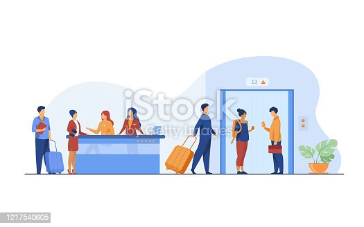 istock Tourists with luggage waiting at hotel reception desk 1217540605