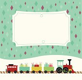 A colorful retro styled toy train carrying little presents travels in the snow in front of a decorative placard.