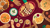 Family celebrating Diwali at home with lamps and traditional food, top view