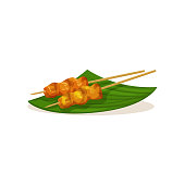 Traditional Malaysian snacks on wooden sticks. Appetizing street food on green banana leaf. Asian cuisine. Culinary theme. Cartoon vector icon. Illustration in flat style isolated on white background.