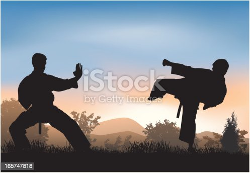 Two athletes simulate combat in nature.Dressed in kimono for martial arts.