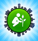 Tree Planting   on Rural Cityscape Skyline Background. The button is in the center of the illustration. a detailed 100% vector rural cityscape skyline is placed around the circumference of the button and includes various houses, single family homes, residential condominium and other suburb buildings. There is a blue sky background with a star burst glow rendered behind the buildings. The image is ideal for displaying rural suburban life concepts and ideas.