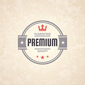 Vintage multicolored Trendy badge (Premium, Guaranteed Quality) (Red, gray), isolated on a brown retro background with an effect of old textured paper. Elements for your design, with space for your text. Vector Illustration (EPS10, well layered and grouped). Easy to edit, manipulate, resize or colorize.