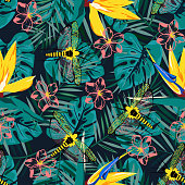 abstract seamless pattern with yellow flowers of strelitzia and dragonflies on black, bright flower background