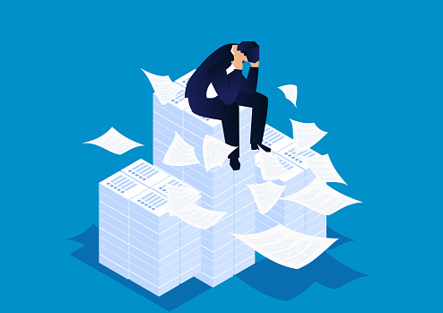 Troubled businessman sitting on a large pile of documents, under heavy and hard work pressure
