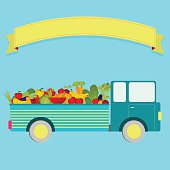 Truck carrying vegetables and fruits. Blank ribbon for insert text.
