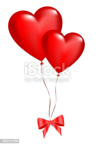 istock Two balloons in the shape of hearts on a white 903224786