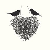 two birds making heir nest - love and labor concept