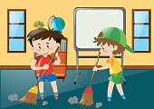 Two boys sweeping classroom floor