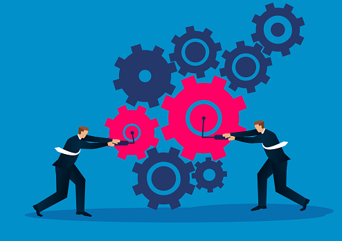 Two businessmen work together to make the gears work