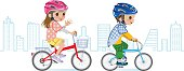 Two children riding Bicycle, Helmet, Cityscape background.