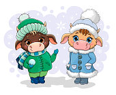 Two cute little cartoon cows in winter clothing standing in the falling snow in warm coats, boots, hats and scarf, colored vector illustration