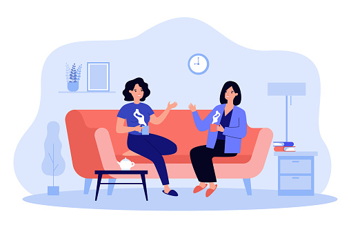 Two female friends drinking tea at home