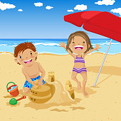 Two kids building a sand castle in summer beach.