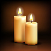 Two lit white wide candles against a simple brown background
