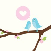 Two little blue love birds sitting on a spring branch with pink blossom and green leaves. One sings a love song to the other.