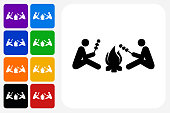 Two People Next to Campfire Icon Square Button Set. The icon is in black on a white square with rounded corners. The are eight alternative button options on the left in purple, blue, navy, green, orange, yellow, black and red colors. The icon is in white against these vibrant backgrounds. The illustration is flat and will work well both online and in print.