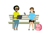 Two teen girls with gadgets are sitting on the bench,isolated on white background