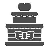 istock Two tiered cake with heart and bow solid icon, Birthday cupcake concept, wedding cake sign on white background, Bunk cake with bow and heart icon in glyph style for mobile. Vector graphics. 1283972984