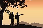 Two tourists standing under a tree pointing in the distance in mountain landscape with orange sky and space for your text - vector