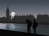 Two tourists with backpacks on the Thames River in London at Westminster Palace and Big Ben, with flying seagull