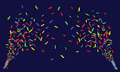 Two crackers with confetti on a dark background, holiday, serpentine