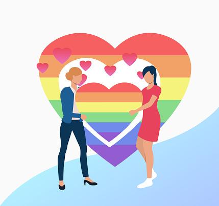 Two women holding rainbow heart
